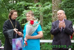 Награду В. Колосовой вручает священник Р. Манилов.